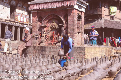 Woman placing pottery jars in the Town Square to dry. Bkaktapur, Nepal.