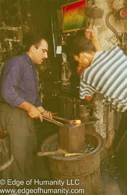 Ironsmith pounding metal. Aleppo, Syria.