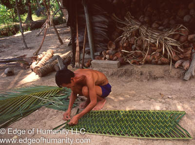 Man building a panel out of coconut fronds - Mekong River, Vietnam.