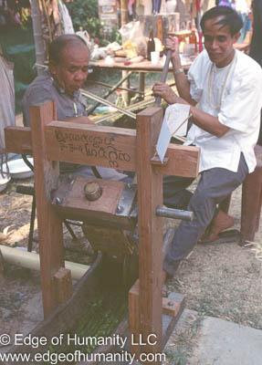 Men working a pressing machine in Thailand.