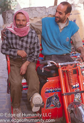 Two men moving around on a tricycle - Syria.