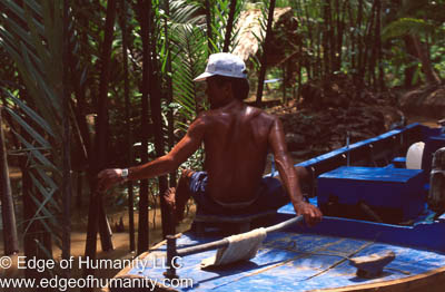 Man maneuvering a boat in the Mekong River, Vietnam