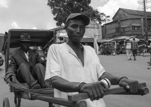 A hand-drawn rickshaw driver and his passenger, Ambositra, Madagascar