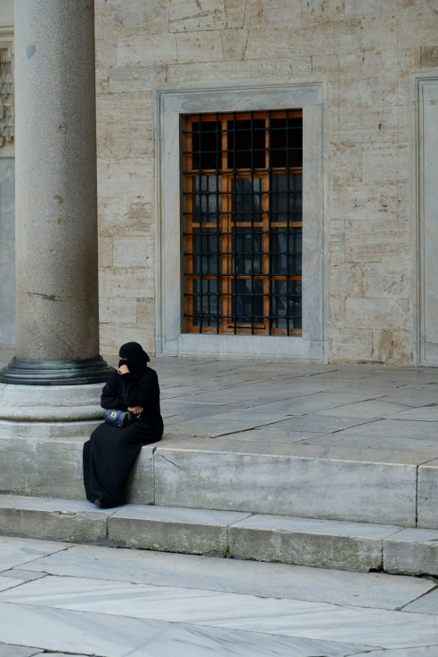 Sultanahmet Camii - a mosque visitor takes a break from photographs in the courtyard of the Blue Mosque.