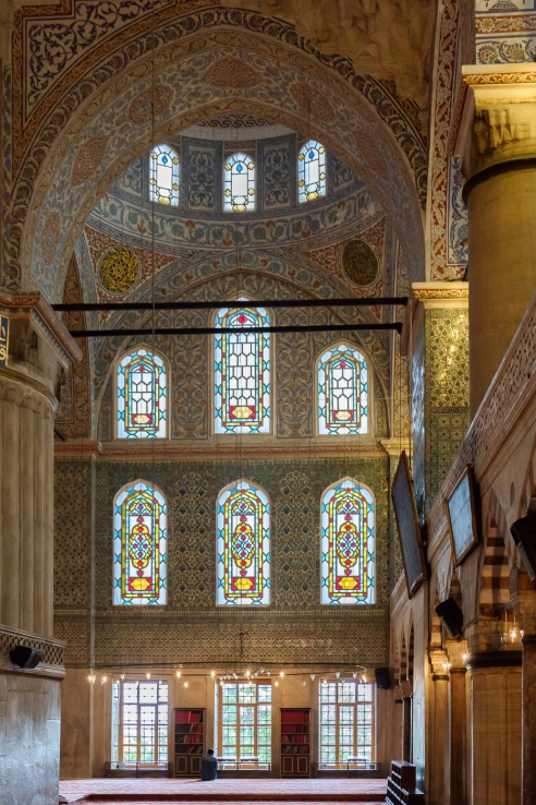 Sultanahmet Camii - a man stays on after prayer in the prayer hall.