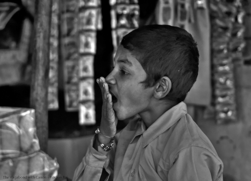 """This was a shot at Agra near Taj Mahal. This kid was working on road side Chai shop which also sold tobacco, cigarette, etc.  He was also having a conversation with another photo buddy of mine. I don't remember what made him give """"surprised"""" but I remember the moment when he asked for my Canon camera to hold and feel it - India."""