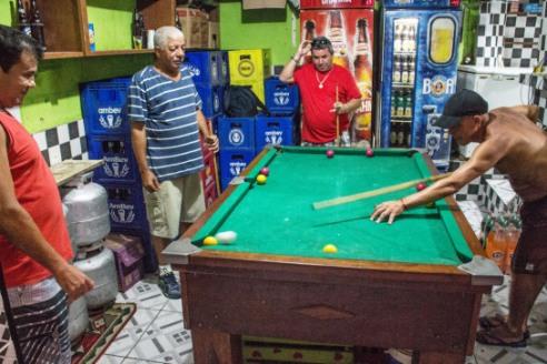 Pool players, little space but fun - Rocinha Slum (Favela), Rio de Janeiro, Brazil.
