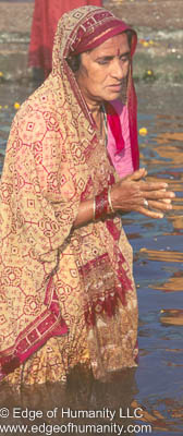 Woman praying in the Ganges River, Varanasi, India.