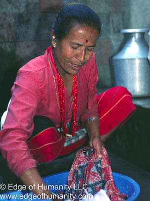 Woman doing laundry in a small plastic tub - Nepal.