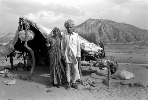 . Father and mother portrait in front of their home Rural Rajasthan, India