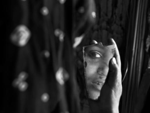 Gypsy girl is looking at herself in broken piece of mirror Rural Rajasthan, India
