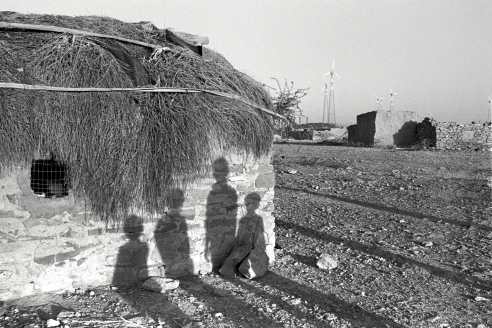 Shadows of the children on the house in the desert with the wind turbines in the background Rural Rajasthan, India