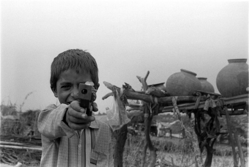Young boy is playing with a toy guy Rural Rajasthan, India
