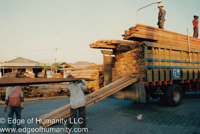 Loading wood in the back of a truck by hand. Lumber yard, Indonesia.