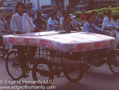 Man transporting a mattress on a tricycle cart in the middle of traffic - Vietnam.