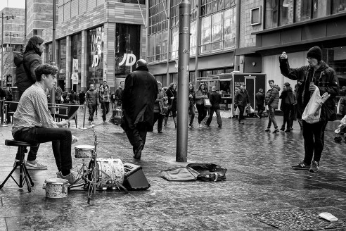 Busker in Liverpool UK playing to one man.