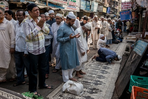 Muslims conduct their afternoon prayers in the streets outside Minara Masjid. As there is not enough space inside the mosque for everyone to pray inside, the streets surrounding the mosque fill up at prayer time.