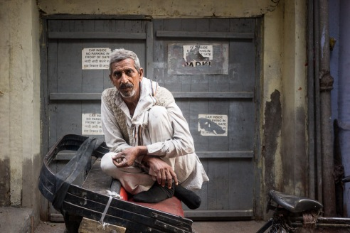 A portrait of a rickshaw wallah sitting on his rickshaw in the quiet back streets of Old Delhi.