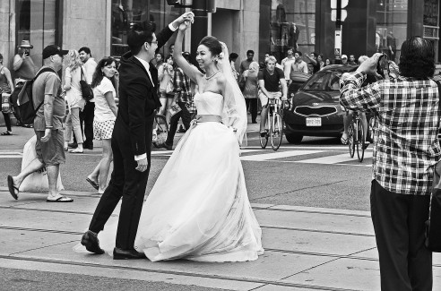A newly married couple takes advantage of the all way stop intersection Yonge and Dundas Toronto