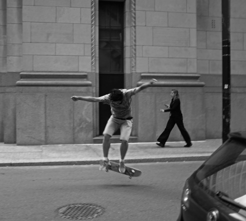 A skateboarder skates and jumps in the Financial District Yonge and King Toronto