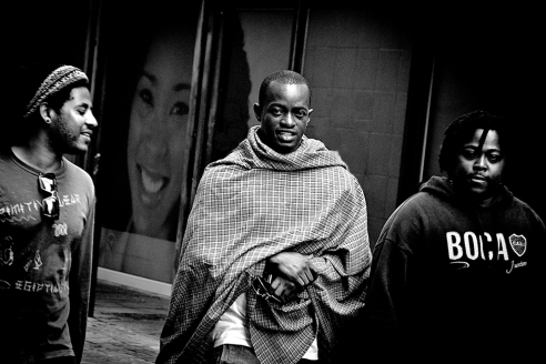 """""""ANGELS & DEMONS""""<br /> Standing on a street corner in Cape Town I saw these three friends walking toward me. Some looked menacing while others light hearted. The gentleman in the middle- looked at me with curiosity. It was for me intriguing. The poster girl in the background inspired the title along with the balance of feelings in the picture."""