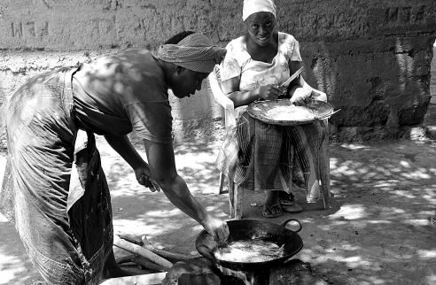 """Frying Fish"" This shot was taken in Moshi, Tanzania the day before my hike up Kilimanjaro. I was exploring the town out in the rural settlements. These two ladies are preparing traditional cooked fish which is hung up to dry."