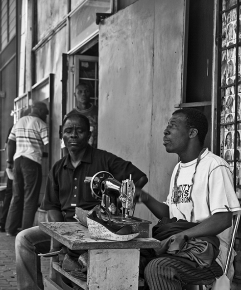 """The tailor on main"" This shot is of a man doing tailor work on main road, New Town, Johannesburg. I just loved the way the streets are alive with culture and vibe. This man is putting his trade to direct use to the public right on the road. Hats off to him"