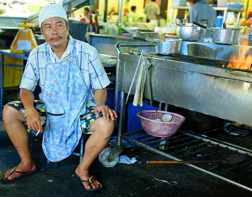 Cook - Thai cook takes a well earned rest from the heat. Hua Hin, Central Thailand.