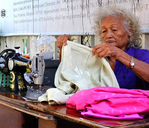 Sewing lady - Everyday this elderly lady pushed her handcart along the Sukhumvit road in Bangkok to earn money by repairing other peoples garments. Thailand