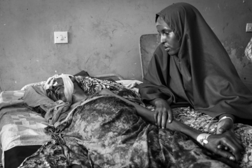 After being shot in the head during a battle between Al-Shabaab militants and AMISON troops, 61 year-old Abdulkadir Dahir lies in a coma since he was brought to the Banadir Hospital three days ago. His daughter Yasmeen is by his side. Mogadishu, Somalia.