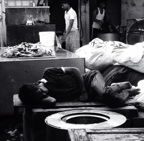 Bed room on the move, a tired assistant washer man sleeps in a cramped corner inside the lanes of Dhobi Ghat