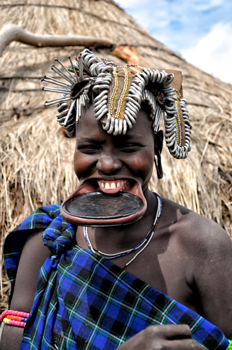A Mursi woman laughing with traditional plate. For women of this tribe the lip plate is a beauty ornament. Omo river valley, Ethiopia.