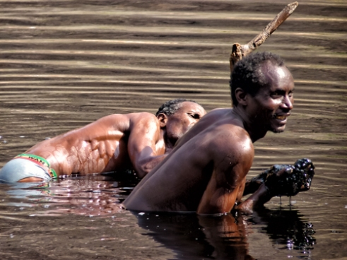 """Borana men collect salt with bare hands in a salt lake. The salt is called """"black gold"""". Ethiopia."""