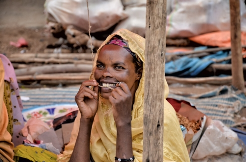 A woman in a market cleans her teeth with a piece of string. Harar, Ethiopia.