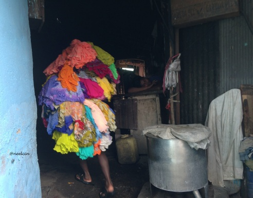 Piled Up-A washerman carries a huge volume of clothes from one section to the other in Dhobi Ghat