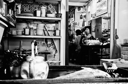 The fate of fish: A fish is frying as a woman in the distance is lost in her thoughts in Busan (Korea's second city).