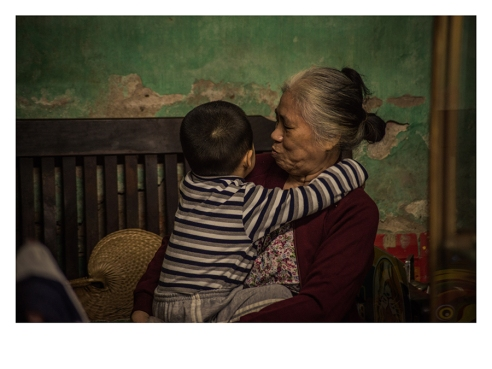 A grandmother plays with her grandson. HCMC, Vietnam