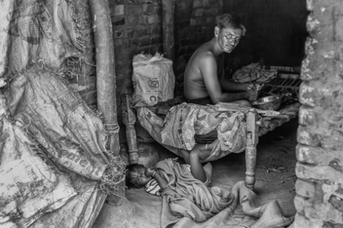 Here a Dafer father was cutting vegetable while the child played on the floor.