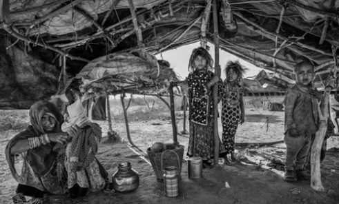 Vasfoda woman with her children at home. At night they would put the blankets (seen on the pile) on the floor to sleep on. Many of these makeshift tents are swept away in Monsoon rains.