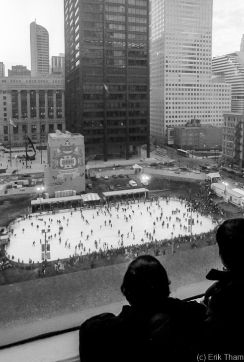 Chicago, IL: Two children watch the ice rink in downtown Chicago from a window of the Marshall Field's department store.