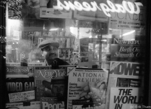 Chicago, IL: A newspaper man during late evening inside his little kiosk in downtown Chicago.