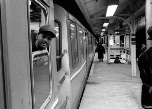 Chicago, IL: A train conductor is checking the platform before his Chicago El Train leaves the nocturnal Fullerton station.