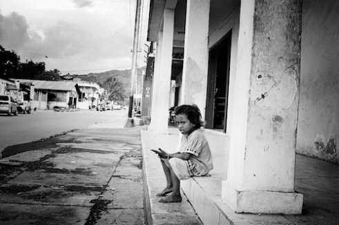 Timor Leste: A girl sits alone in a street in Culuhun, just outside the country's capital of Dili. Poverty and malnutrition plagues the country as does corruption.