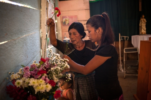Isabel (16), together with her grandmother Juliana, who arrived at the rubbish dump with the first families around 20 years ago, decorate the small catholic church, that the community has built with recycled materials, with flowers they bought, as Isabel's child Alejandra is watching. Juliana earns around 15 to 20 Mexican Pesos (1 to 1,3 Dollars per day), the flowers she bought cost 30 Pesos.