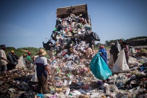 Women and men are waiting for a garbage truck to unload waste from Tapachula at the municipal rubbish dump. During their work, they are exposed not only to bad smell and toxic materials that, according to local activists are unloaded by corporations in the rubbish dump, but also to the direct impact of sunlight at temperatures that can reach 40 degree Celsius.