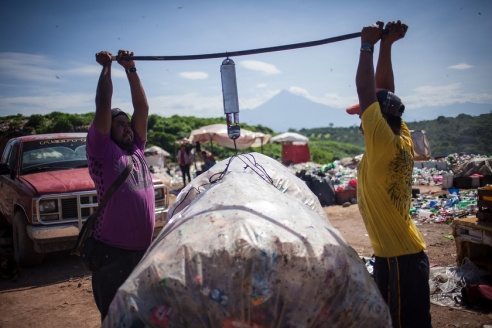 "Emmanuel (left), who works with one of the 3 corporations that buys waste at the rubbish dump, is weighting a bag of PET plastic to calculate the revenue that will be paid to the gatherer. Emmanuel, of Mexican origen, migrated undocumented to the United States, where he worked in Orlando (Florida) for 3 years to pay off a debt. ""Over there, its like living in a prison"", he resumes his experience. Today he earns 150 Mexican Pesos (10 US Dollars) per day, his wife is expecting their second child."