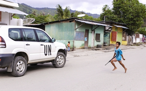 Timor Leste: A boy runs with a 'toy' gun towards a UN vehicle in Culuhun in 2014. This image won the International Loupe Award for Photojournalism in 2014.