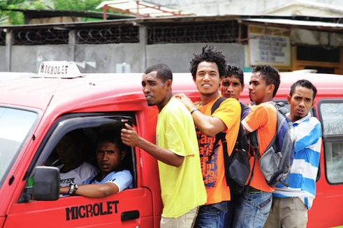 Timor Leste: Young people catch a ride on a 'microlet' back to their villages from the country's capital of Dili.