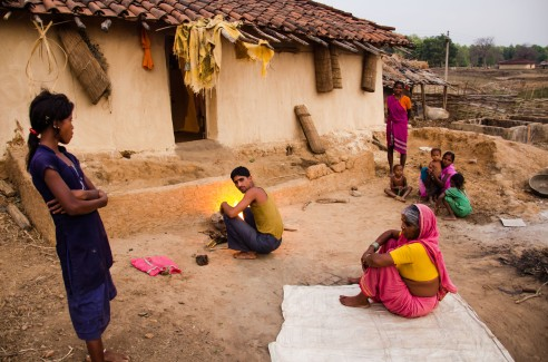 The man in the centre is cooking fish for his family of fourteen members. The walls of the house are lined with fish traps made out of bamboo which are present in every typical Baiga household. Baiga Tribe Village outside Kanha National Forest in Madhya Pradesh, India.