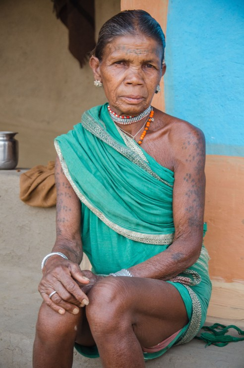 Traditionally a sect of the tribe called the Nanga Biaga wore no clothes but women now cover up with a saree (with or without a blouse). A typical Baiga woman wears her saree above the knees and has her body and face covered in identifiable tattoos with shapes like triangles, dots and circles. Baiga Tribe Village outside Kanha National Forest in Madhya Pradesh, India.